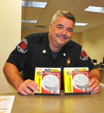 Fire Fighter Holding Two Smoke Detectors