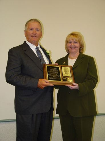 A man and a woman holding a plaque.