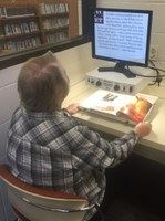 A person using the AT Lab Video Magnifier